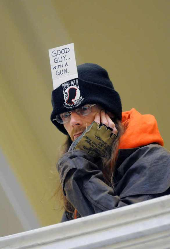 Geno Apeman, of Boise, shows his support for gun rights on his cap as he watches a Guns Across America Rally from the third floor rotunda inside the Idaho Statehouse on Saturday, Jan. 19, 2013 in Boise.  Rallies are being held by gun rights advocates four days after President Barack Obama unveiled a sweeping plan to curb gun violence.  (AP Photo/Idaho Press-Tribune, Adam Eschbach) MANDATORY CREDIT