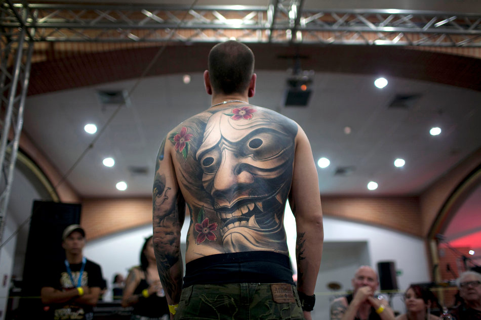 A unidentified man shows his tattoos as he attends Venezuela Expo Tattoo in Caracas, Venezuela, Saturday Jan. 28, 2012. (AP Photo/Ariana Cubillos)