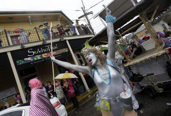 Revelers dance in the street as rain starts to fall on Mardi Gras day in the Faubourg Marigny section of New Orleans, Tuesday, Feb. 12, 2013.  Despite threatening skies, the Mardi Gras party carried on as thousands of costumed revelers cheered glitzy floats with make-believe monarchs in an all-out bash before Lent.   Crowds were a little smaller than recent years, perhaps influenced by the forecast of rain. Still, parades went off as scheduled even as a fog settled over the riverfront and downtown areas.  (AP Photo/Gerald Herbert)