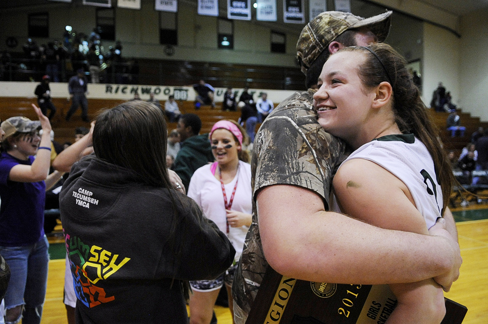 NICK SCHNELLE/JOURNAL STAR  Maddie Pierce (33) of Richwoods is hugged by Tyler Brown, a senior at Richwoods, after defeating United Township, 57-42, on Friday at a Class 4A Regional Championship game at Richwoods High School.