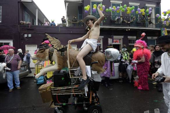 A man dressed in a diaper rides a mechanical dog with wings in the French Quarter during Mardi Gras in New Orleans, Tuesday, Feb. 12, 2013.  Despite threatening skies, the Mardi Gras party carried on as thousands of costumed revelers cheered glitzy floats with make-believe monarchs in an all-out bash before Lent.   Crowds were a little smaller than recent years, perhaps influenced by the forecast of rain. Still, parades went off as scheduled even as a fog settled over the riverfront and downtown areas. (AP Photo/Gerald Herbert)