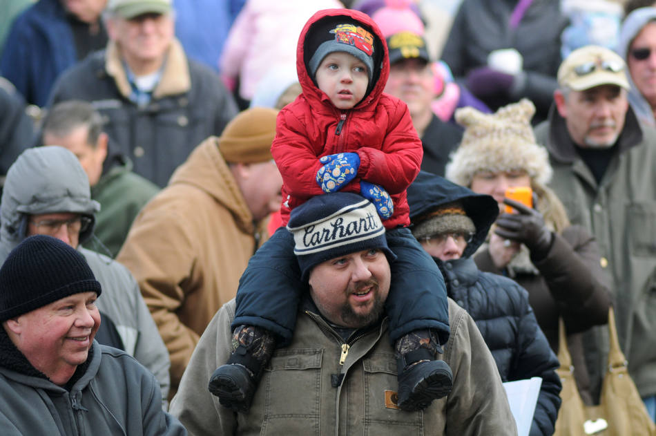 Nathan Schwartz, Minersville, Pa., sits on the shoulders of his father Jerry Schwartz for a better view in below freezing temperatures after Pine Grove Grundsau Lodge No. 5's stuffed Groundhog Grover and his bride Sweet Arrow Sue predicted six more weeks of winter during the annual Groundhog Day Celebration in Pine Grove, Pa., Saturday, Feb. 2, 2013. At left is Gerry Schwartz, Pine Grove, Pa. (AP Photo/The Republican-Herald, Jacqueline Dormer)