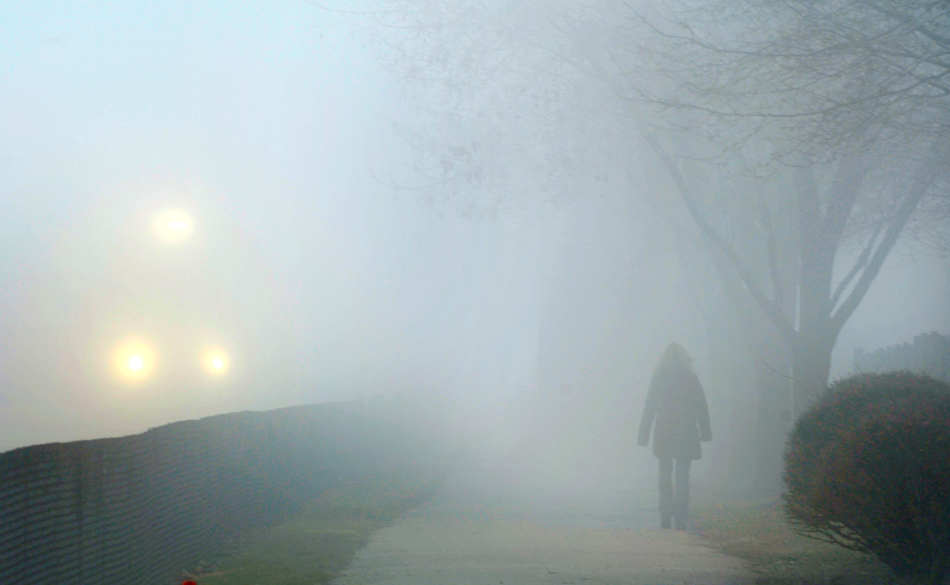 DAVID ZALAZNIK/JOURNAL STAR  A woman walks into the fog blanketing  downtown Peoria as a southbound freight train passes the Gateway Building.
