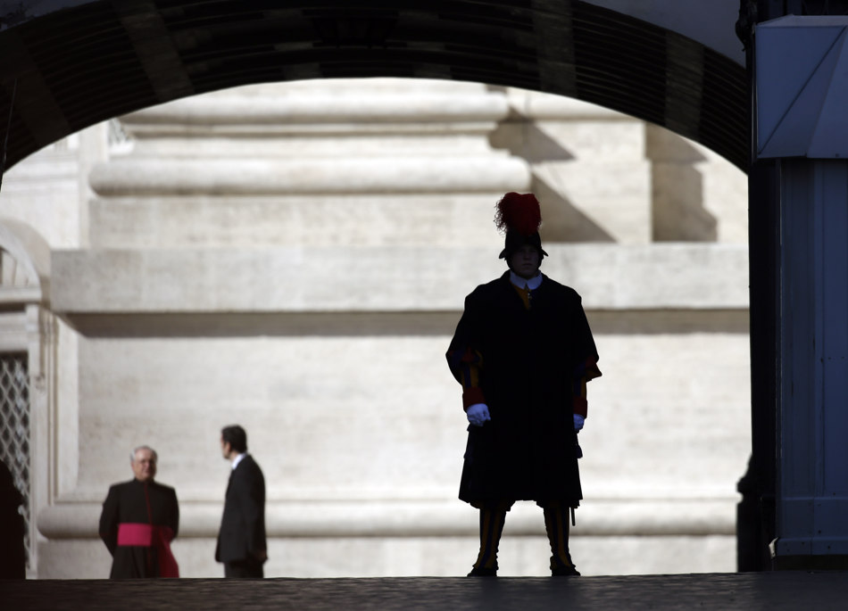 A Swiss guard, right, is silhouetted in St. Peter's Square at the Vatican, Wednesday, Feb. 27, 2013. Pope Benedict XVI is preparing for his final general audience, the weekly appointment he kept with the faithful and tourists to teach them about the Catholic faith. (AP Photo/Gregorio Borgia)
