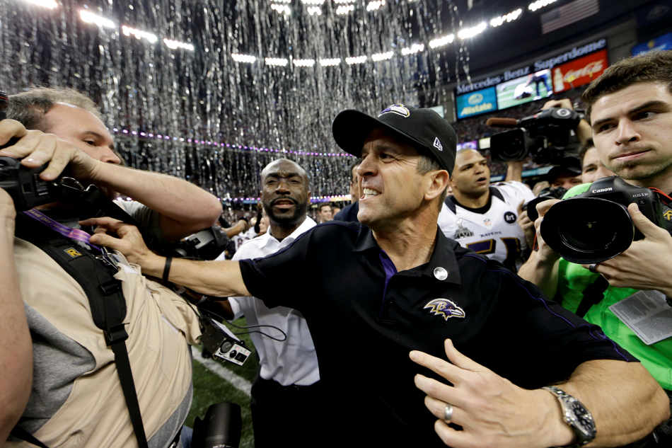 Baltimore Ravens head coach John Harbaugh pushes a photographer after their 34-31 win against the San Francisco 49ers in the NFL Super Bowl XLVII football game, Sunday, Feb. 3, 2013, in New Orleans. (AP Photo/Dave Martin)