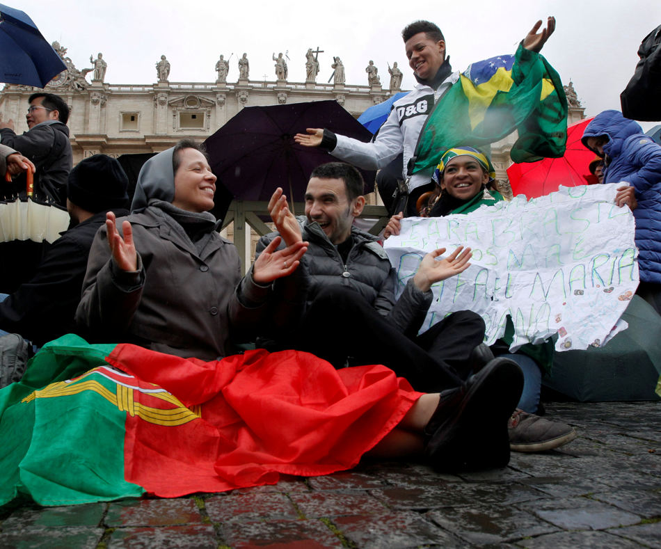 Pilgrims wait in St. Peter's Square as cardinals meet in conclave to elect a new pope at the Vatican, Wednesday, March 13, 2013. Black smoke billowed from a chimney on the Sistine Chapel earlier in the day signifying that a pope had not yet been elected.  (AP Photo/Dmitry Lovetsky)