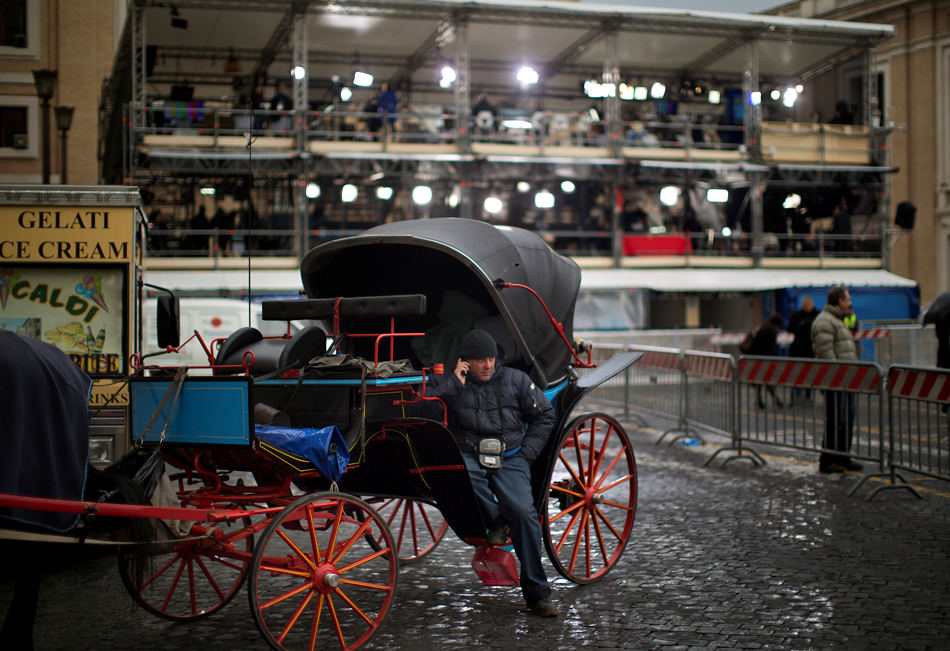 A coachman waits for customer near a stage set up to host TV crews in front of St. Peter's Square on the second day of the conclave to elect a new pope, at the Vatican, Wednesday, March 13, 2013.  Black smoke again billowed from the chimney of the Sistine Chapel on Wednesday, meaning that Catholic cardinals hadn't elected a pope on their second or third rounds of balloting. (AP Photo/Emilio Morenatti)