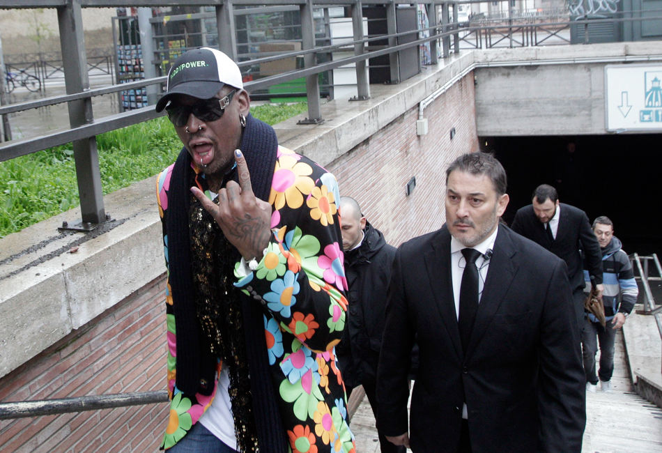 Former NBA star Dennis Rodman walks out of a     a street near St. Peter's Square at the Vatican, Wednesday, March 13, 2013. Rodman is in Rome to promote the papal candidacy of Cardinal Peter Turkson of Ghana. ((AP Photo/Riccardo De Luca)