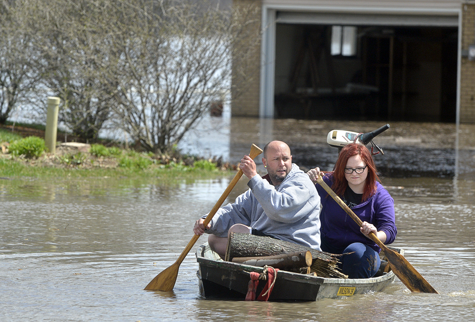Chad Keedy and stepdaughter Jordan DeBolt, 15, of Chillicothe, Ill., paddle through flood waters in their neighborhood along Oak Lawn Steet in Chiilicothe on Saturday, April 20, 2013. The Illinois River continues to rise after heavy rains earlier in the week.(AP Photo/Peoria Journal Star/Ron Johnson)