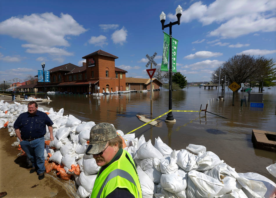 AP Photo/Seth Perlman Peoria Maintenance Engineer Jim Clark, right bottom, monitors the sand bag wall holding back the Illinois River from recent flooding Wednesday, April 24, 2013, in Peoria, Ill. The Illinois River finally crested Tuesday at 29.35 feet, eclipsing a 70-year record in Peoria.