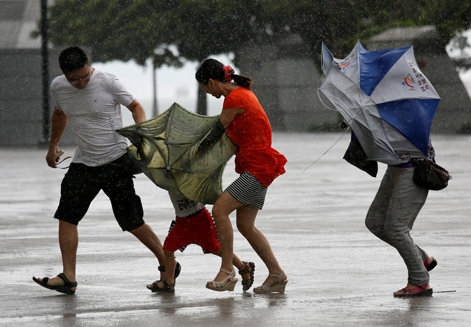 A family battle against the strong wind near the waterfront in Hong Kong Wednesday, Aug. 14, 2013. Typhoon Utor lashed Hong Kong with wind and rain, closing down the bustling Asian financial center Wednesday before sweeping toward mainland China. (AP Photo/Vincent Yu)