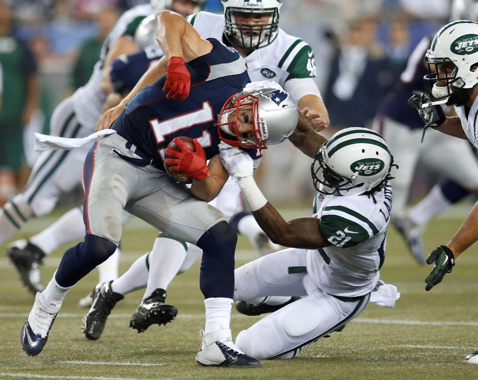 New York Jets defensive back Ellis Lankster (21) tries to tackle New England Patriots wide receiver Julian Edelman (11) during the second quarter of an NFL football game Thursday, Sept. 12, 2013, in Foxborough, Mass. (AP Photo/Elise Amendola)
