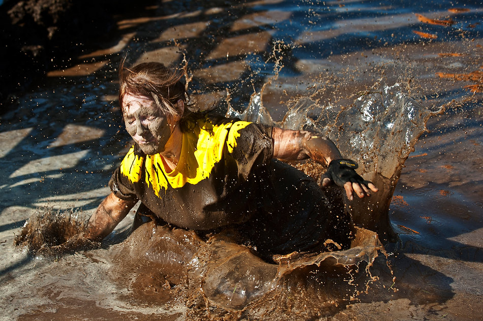 JUSTIN WAN/JOURNAL STAR Jill Daugherty of Peoria falls into a mud pit, Saturday morning at Three Sisters Park in Chillicothe during Hard Charge obstacle race.