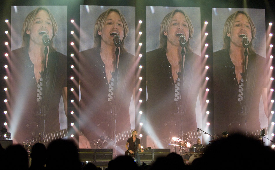 MATT DAYHOFF/JOURNAL STAR  Country music star Keith Urban performs in front of several giant video screens Sunday night at the Peoria Civic Center.