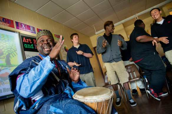 FRED ZWICKY/JOURNAL STAR Nigeria's art ambassador, Ibiyinka Olufemi Alao, shares a traditional song as he coaxes students at Harrison Primary School to dance during a visit on Nov. 4.