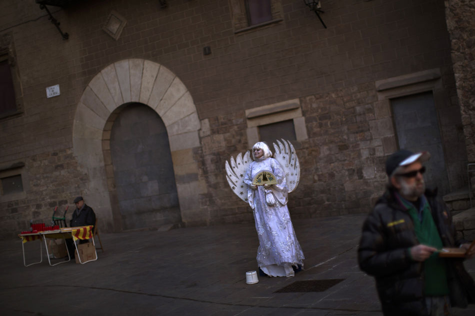 A woman dressed as an angel begs in front of the Barcelona cathedral, Spain, Thursday, Jan. 23, 2014. (AP Photo/Emilio Morenatti)
