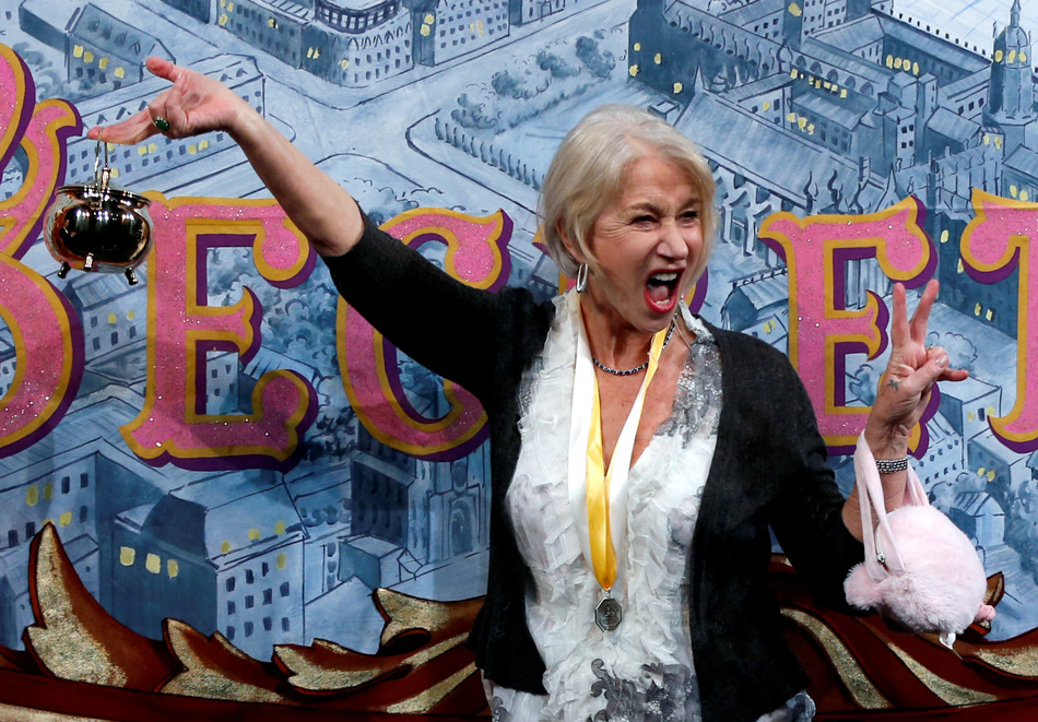 Actress Helen Mirren holds the Hasty Pudding Pot aloft during her roast as woman of the year by Harvard University's Hasty Pudding Theatricals in Cambridge, Mass., Thursday, Jan. 30, 2014. (AP Photo)