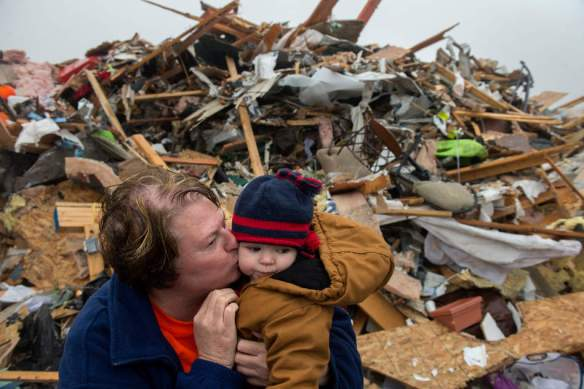 FRED ZWICKY/JOURNAL STAR Jan Briney kisses her grandson Wyatt Briney, 5, amid the tornado debris on Dec. 4 in Washington. Wyatt's family home was destroyed in the EF-4 tornado.