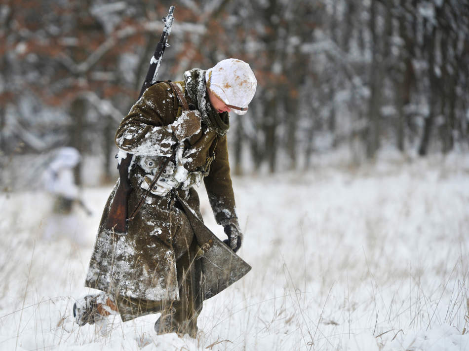 RON JOHNSON/JOURNAL STAR   Noah Thoms of Maroa, portraying a member of the 9th Infantry is covered with snow after falling in battle during a re-enactment of the Battle of the Bulge on Dec. 14 at W.H. Sommer Park in Edwards.