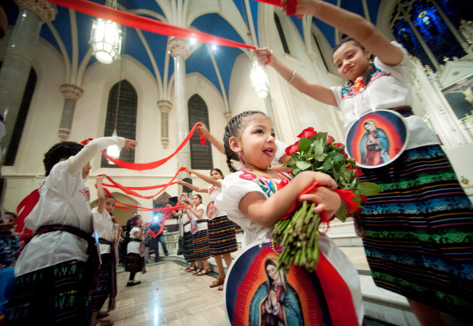 Evelyn Avila, 4, of Peoria dances with roses on Dec. 12 at Saint Mary's Cathedral during the Feast of Our Lady of Guadalupe. Thousands gathered at the Catholic church in downtown Peoria to celebrate the Patron Saint of Mexico.