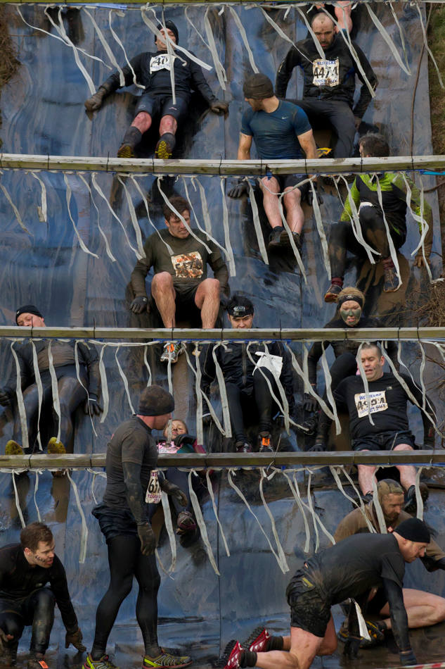 "Competitors make their way down an obstacle during the annual Tough Guy race ""the toughest race in the world"" at Perton in Staffordshire, England, Sunday Jan. 26, 2014. Tough Guy claims to be the world's most demanding one-day survival ordeal. First staged in 1987, the Tough Guy Challenge has been widely described as one of the hardest races of it's type with up to one-third of the starters failing to finish in a typical year. (AP Photo/Jon Super)"