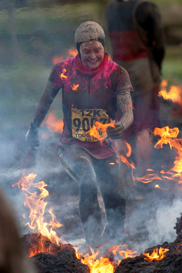 "A competitor jumps through fire during the annual Tough Guy race - ""the toughest race in the world"" - at Perton in Staffordshire, England, Sunday Jan. 26, 2014. Tough Guy claims to be the world's most demanding one-day survival ordeal. First staged in 1987, the Tough Guy Challenge has been widely described as one of the hardest races of it's type with up to one-third of the starters failing to finish in a typical year. (AP Photo/Jon Super)"