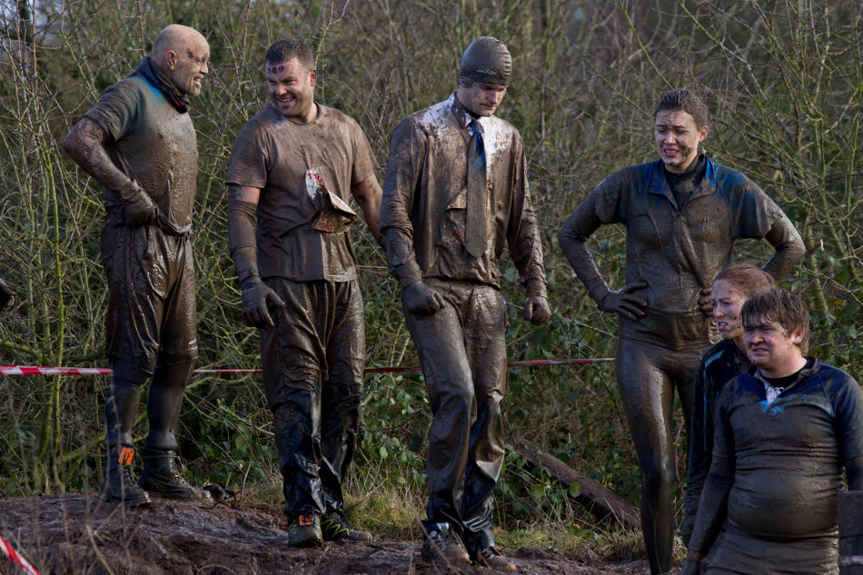 "Competitors covered in mud wait to enter an obstacle during the annual Tough Guy race ""the toughest race in the world"" at Perton in Staffordshire, England, Sunday Jan. 26, 2014. Tough Guy claims to be the world's most demanding one-day survival ordeal. First staged in 1987, the Tough Guy Challenge has been widely described as one of the hardest races of it's type with up to one-third of the starters failing to finish in a typical year. (AP Photo/Jon Super)"