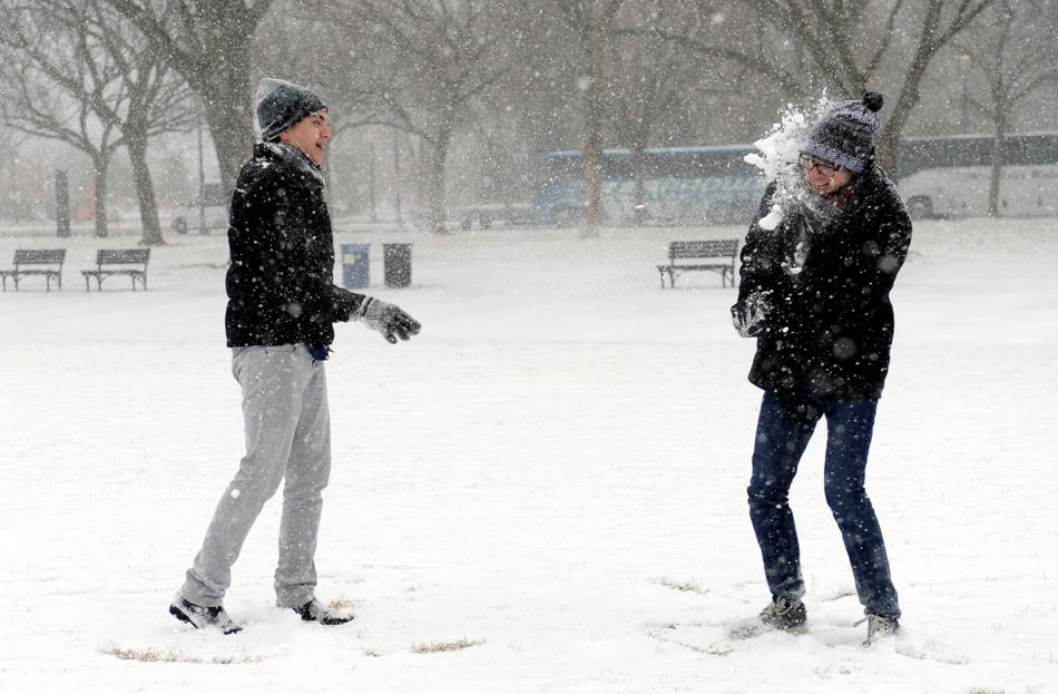 Rick Mendenhall of Albuquerque, N.M., right, gets hit in the face during a snowball fight with his friend Jeff Scott of Los Angeles, left, on the National Mall in Washington during the start of a major snowstorm, Tuesday, Jan. 21, 2014. Many government offices and schools closed before the first flake of snow, but there were signs Tuesday that significant winter weather was moving into the mid-Atlantic region as heavy snow began falling.(AP Photo/Susan Walsh)