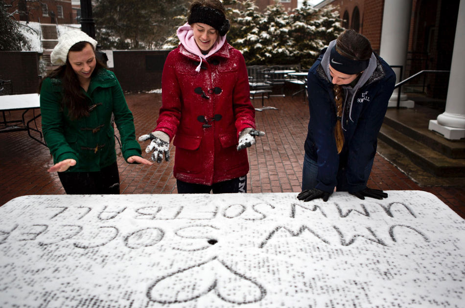University of Mary Washington students Alex Tenney, left, Lauren Strayhorn, center, and Hannah Otterman leave their hand prints in the snow on a table outside UMW's dining hall on Tuesday, Jan. 21, 2014, in Fredericksburg, Va. All classes were canceled due to the snowstorm. (AP Photo/The Free Lance-Star, Autumn Parry)