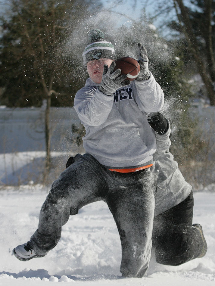 Snow flies into Gerard Kirk's face as he catches a pass during a game of freeze football with his friends Wednesday, Jan. 22, 2014, in New Castle, Del. A winter storm dumped a foot or more of snow and closed schools across much of the Northeast. The storm stretched from Kentucky to New England but hit hardest along the heavily populated Interstate 95 corridor between Philadelphia and Boston. (AP Photo/The Wilmington News-Journal, Andre L. Smith)  NO SALES