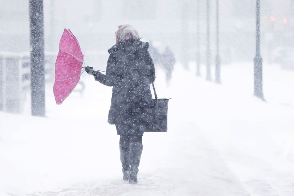 A pedestrian's umbrellas is upset during a winter snowstorm Tuesday, Jan. 21, 2014, in Philadelphia. A storm is sweeping across the Mid-Atlantic and New England. The National Weather Service said the storm could bring 8 to 12 inches of snow to Philadelphia and New York City, and more than a foot in Boston.  (AP Photo/Matt Rourke)