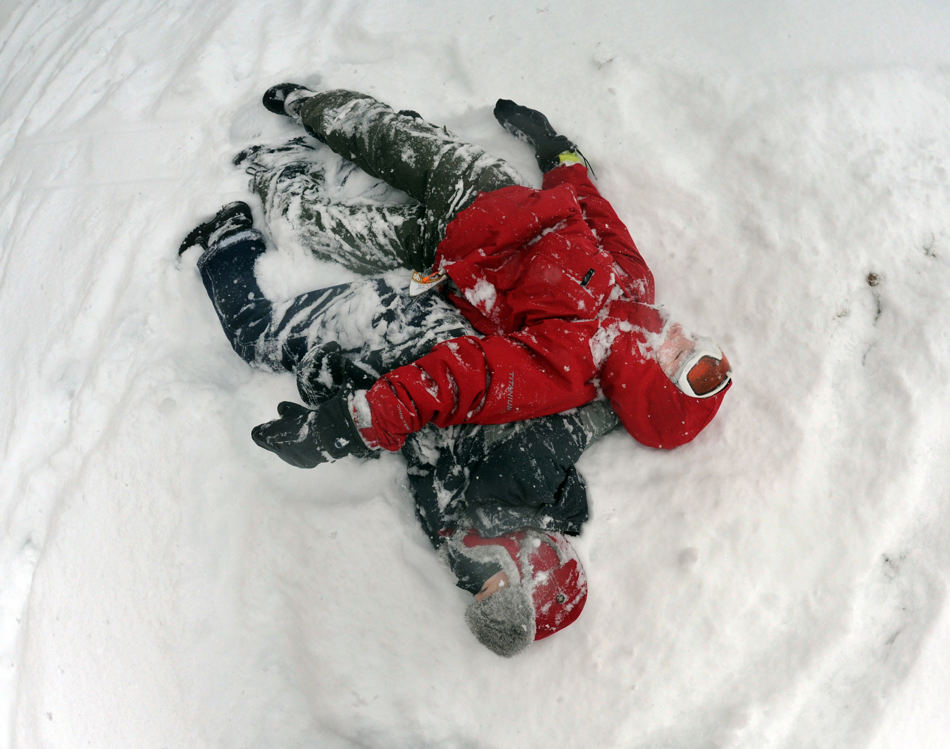 Dyloan Witzig, right, and his brother Zach, catch their breath after wrestling on the hill behind York Suburban High School on Tuesday,  Jan. 21, 2014, in York, Pa. The National Weather Service predicts the storm could drop 8 to 12 inches of snow followed by bitterly cold temperatures. (AP Photo/York Daily Record, Jason Plotkin)  YORK DISPATCH OUT
