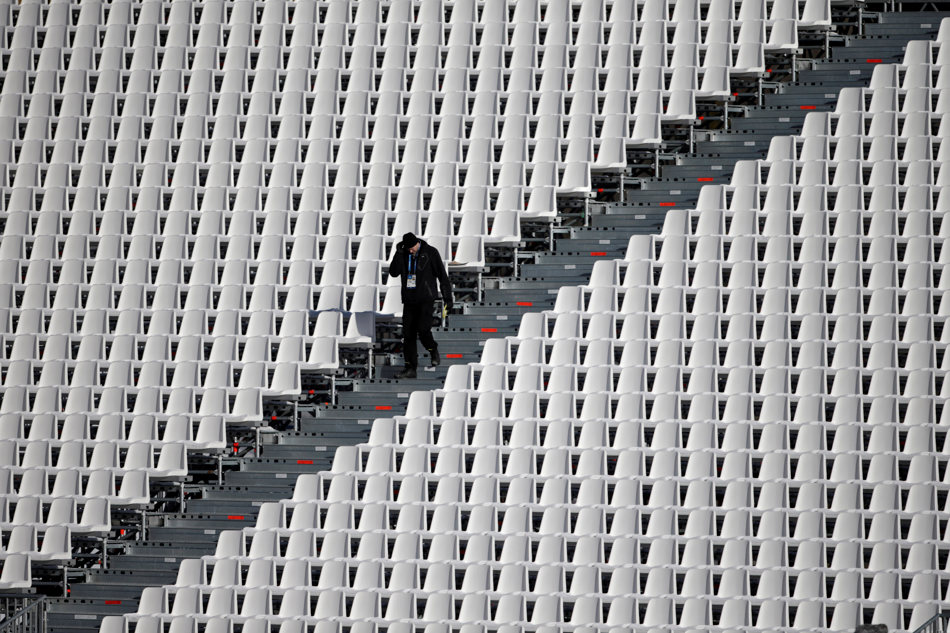 A worker walks in the empty stands of the finish area of the Alpine ski course during final preparations ahead of the Sochi 2014 Winter Olympics, Tuesday, Feb. 4, 2014, in Krasnaya Polyana, Russia.(AP Photo/Gero Breloer)