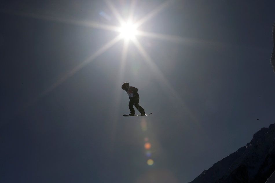 A competitor takes a jump during a Snowboard Slopestyle training session at the Rosa Khutor Extreme Park, prior to the 2014 Winter Olympics, Tuesday, Feb. 4, 2014, in Krasnaya Polyana, Russia. (AP Photo/Andy Wong)