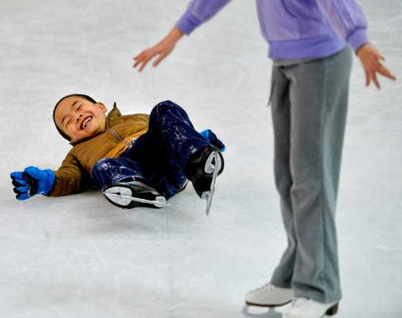 RON JOHNSON/JOURNAL STAR   Timothy Liu, 7, manages a laugh after falling on the ice during skating lessons on Wednesday, Feb. 19 at Owens Center.