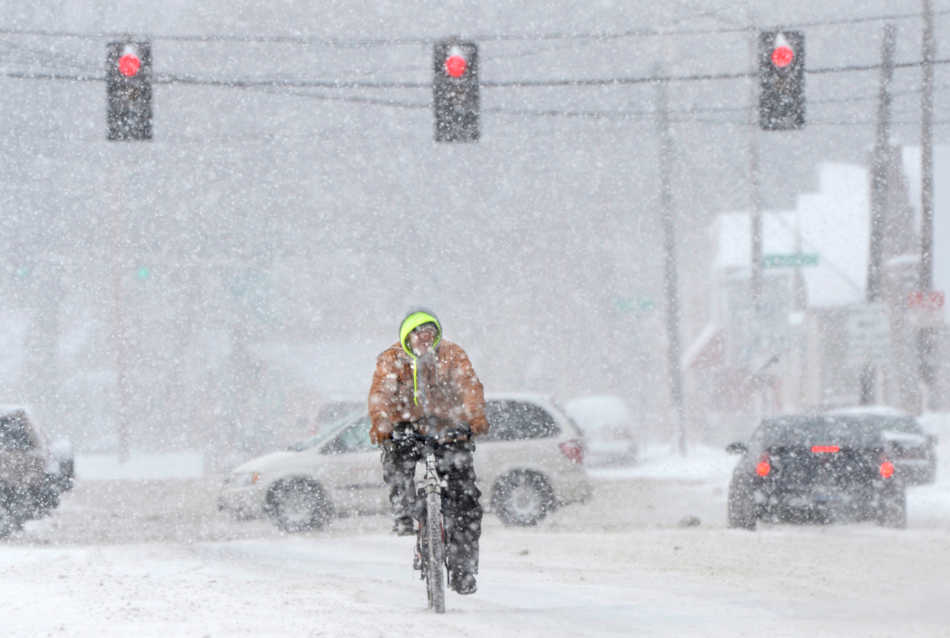 DAVID ZALAZNIK/JOURNAL STAR  A bicyclist steers through a snow shower Wednesday, Feb. 5 on SW Jefferson St. in Peoria.