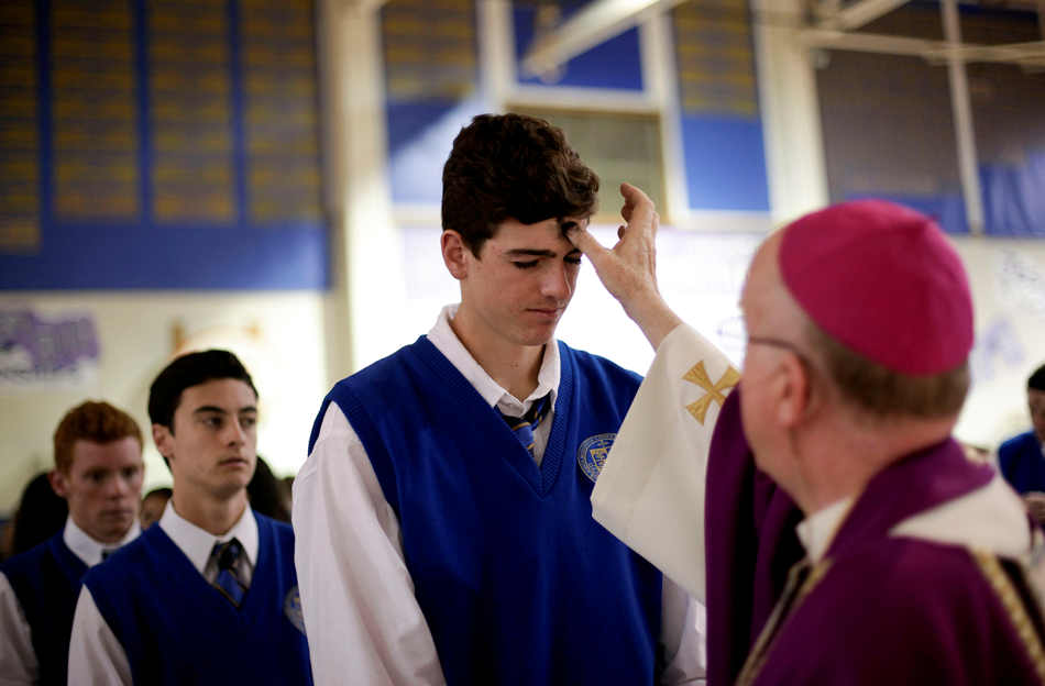 Bishop of Orange, Kevin W. Vann, right, applies ashes to students during an Ash Wednesday Mass at Santa Margarita Catholic High School on Wednesday, March 5, 2014, in Rancho Santa Margarita, Calif. Ash Wednesday marks the beginning of the Lenten season, a time when Christians commit to acts of penitence and prayer in preparation for Easter Sunday. (AP Photo/Jae C. Hong)