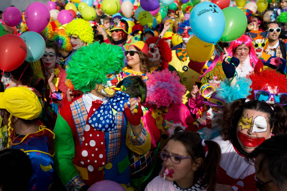 Revelers take part in the carnival Clowns' Parade along the waterfront in Sesimbra, south of Lisbon, Monday, March 3, 2014. Every year on Carnival Monday thousands dress as clowns to take part in the fishing village's parade. (AP Photo/Armando Franca)