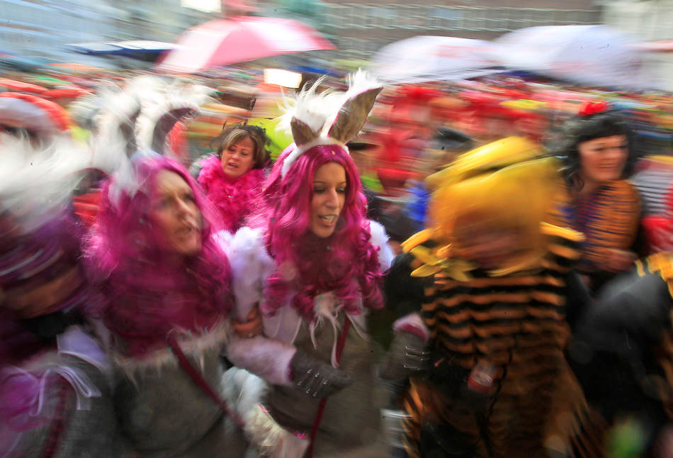 "Revelers dressed in carnival costumes celebrate the start of the street-carnival with its tradition of entering the town halls and women cutting off men's ties with scissors on carnival's so called ""Old Women's Day"" in Duesseldorf, Germany, Thursday, Feb. 27, 2014.(AP Photo/Frank Augstein)"