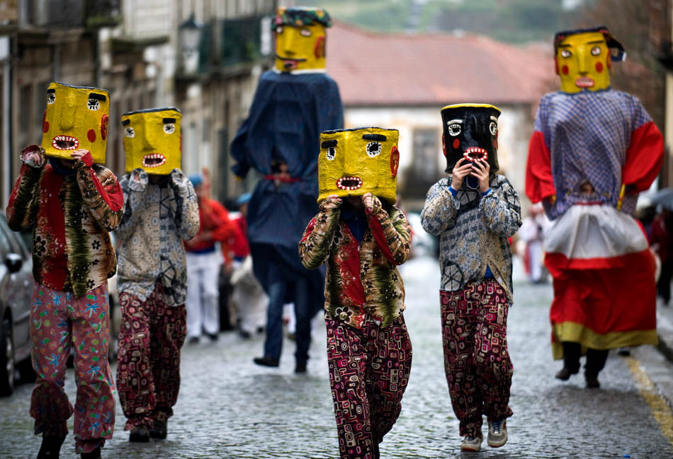 Mask-wearing revelers participate in a Carnival parade in Barcelos, northern Portugal, Sunday, March 2, 2014. Giant puppets and big heads persons, 'Cabecudos' and 'Gigantones' in Portuguese, are basic ingredients of northern pilgrimages, made with a wire frame and wood, coated paper and cloth, covered with plaster and glue and paint. (AP Photo/Paulo Duarte)