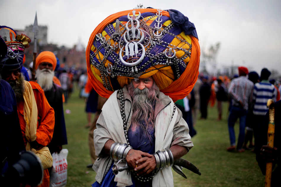 A Sikh warrior, wearing a huge turban attends the annual fair of 'Hola Mohalla' in Anandpur Sahib, in the northern Indian state of Punjab, Monday, March 17, 2014. Believers from various parts of northern India collect at the religious fair to celebrate the festival of Holi in a tradition set by the tenth Sikh guru Guru Gobind Singh in the seventeenth century. Nihangs, or Sikh warriors, display their martial skills and attire during the fair, believed to be maintained in the exact tradition as set by the Guru. (AP Photo/Altaf Qadri)
