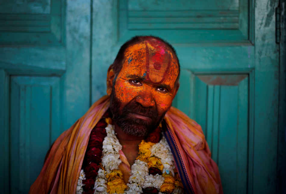 A Sadhu or Hindu holy man leans against a closed door at the Nandagram Temple famous for Lord Krishna during Lathmar Holi festival in Nandgaon 120 kilometers ( 75 miles) from New Delhi, India, Monday, March 10, 2014. According to tradition which has its roots in Hindu mythology men from Barsana arrive at the temple where they are soaked in colored water by men from Nandgaon, believed to be Lord Krishna's village, and then beaten by the women of the village with wooden sticks as they depart the town. (AP Photo/Altaf Qadri)
