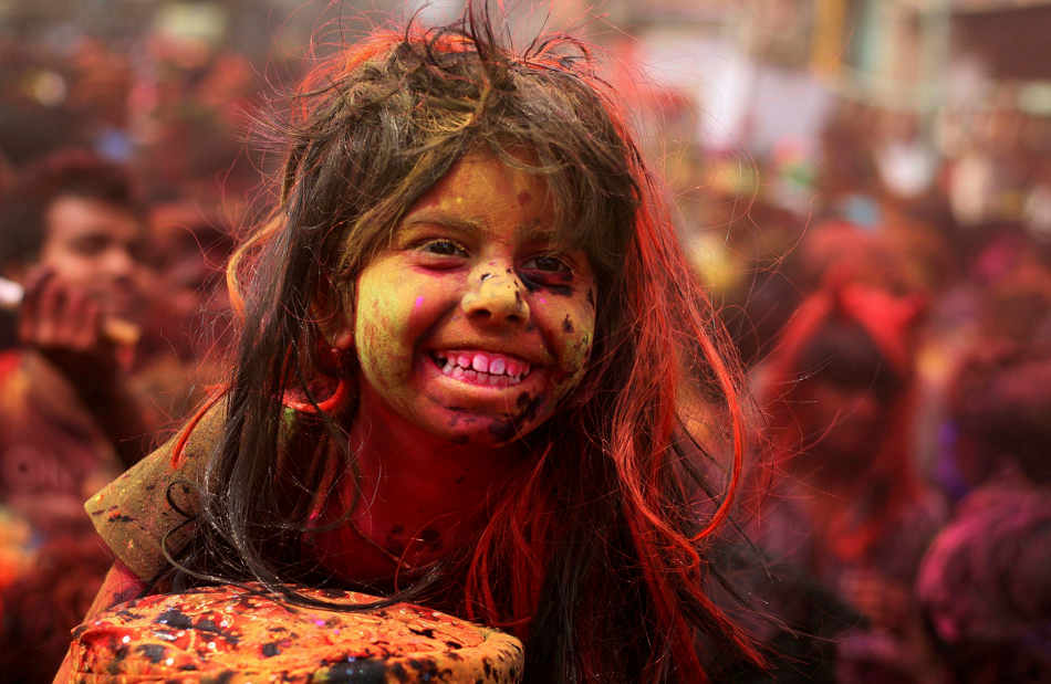 An Indian girl, face smeared with colored powder, sits on the shoulder of her father during celebrations marking Holi, the Hindu festival of colors, in Gauhati, India, Monday, March 17, 2014. The festival also marks the advent of spring. (AP Photo/Anupam Nath)