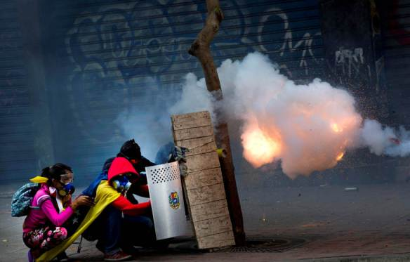 Anti-government protesters shield themselves as they launch a firework at the Bolivarian National Police during clashes in Caracas, Venezuela, Thursday, April 17, 2014. Opposition protesters are demonstrating against high crime, high inflation and shortages of basic goods. (AP Photo/Ramon Espinosa)