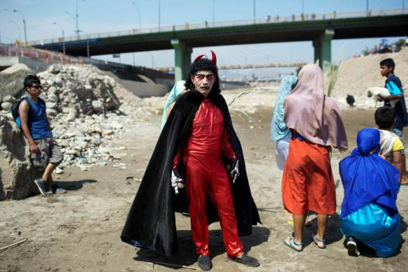 An actor dressed in a devil costume stands on the shores of the Rimac River in Lima, Peru, Thursday, April 17, 2014. The actor performed for people after they attended the reenactment of Jesus' baptism in the river as part of during Holy Week celebrations. (AP Photo/Rodrigo Abd)