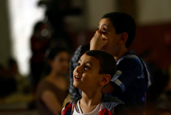 In this late Saturday, April 19, 2014 photo, children celebrate Christianity's most joyous day, during an Easter Eve service presided over by Coptic Pope Tawadros II, at St. Mark's Cathedral, in Cairo, Egypt. Millions of Christians  around the world are celebrating Easter  commemorating the day when according to Christian tradition Jesus was resurrected in Jerusalem two millennia ago. (AP Photo/Ahmed Gomaa)