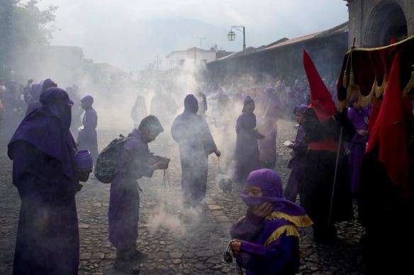 Penitents burn incense during a procession by Saint Francis church as part of Holy Week celebrations in Antigua Guatemala, Thursday, April 17, 2014. (AP Photo/Moises Castillo)