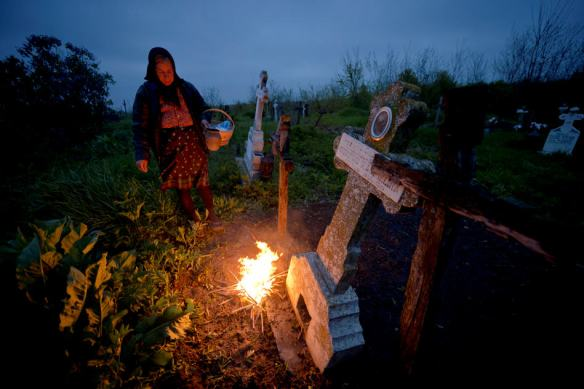 A woman stands by a fire she lit near a grave in the village of Copaciu, southern Romania, early Thursday, April 17, 2014. Part of a Holy Week tradition, Romanians visit, on Maundy Thursday, the graves of their loved ones, light fires and share food with community members in memory of the departed. Orthodox and Catholic worshipers celebrate Easter on on April 20.(AP Photo/Andreea Alexandru/ Mediafax) ROMANIA OUT