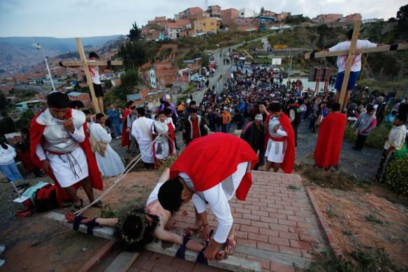 Actor Israel Montenegro is tied to the cross before being crucified, while reenacting the Passion of Christ on a hill above La Paz, Bolivia, Friday, April 18, 2014. Bolivian Catholics joined Christians around the world in celebrating Holy Week and preparing for Easter Sunday. (AP Photo/Juan Karita)