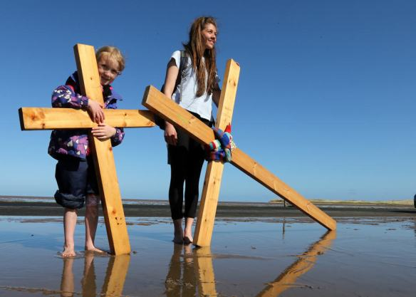 Pilgrims walk with crosses as the Northern Cross pilgrimage makes its final leg of the journey to Holy Island, Berwick Upon Tweed, England, Friday, April 18, 2014. For more than 30 years, groups of pilgrims celebrate Easter by crossing the tidal causeway during the annual Christian cross carrying pilgrimage to Holy Island , the pilgrims walk around 100 miles through Northumberland and the Scottish Borders during Holy Week. (AP Photo/Scott Heppell)